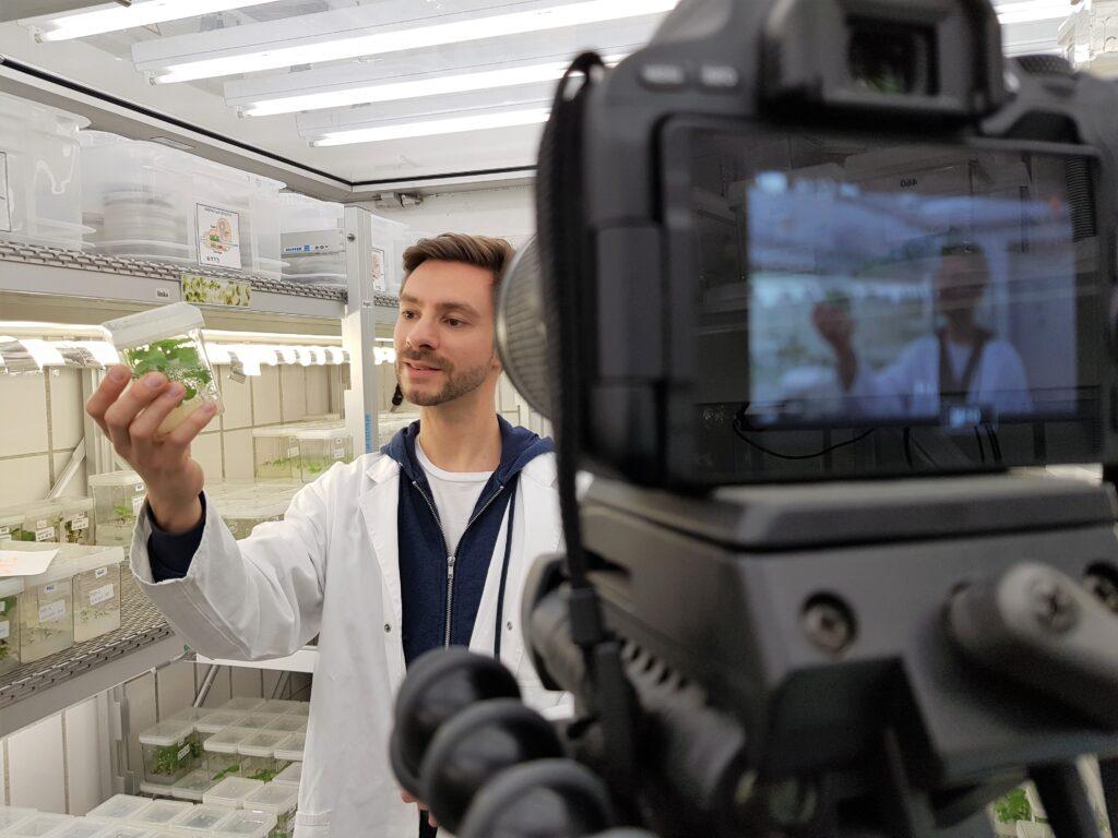 Wissenschaftler im Kittel vor der Kamera mit einer Pflanzenkultur in der Hand
